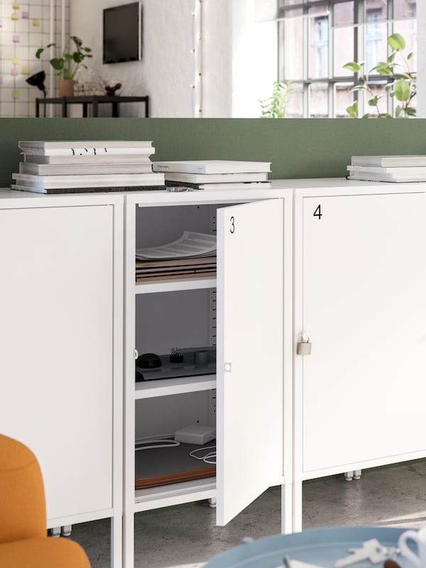 Una fila di mobili bianchi numerati e chiudibili con lucchetto, un'anta aperta mostra documenti e altri oggetti all'interno - IKEA