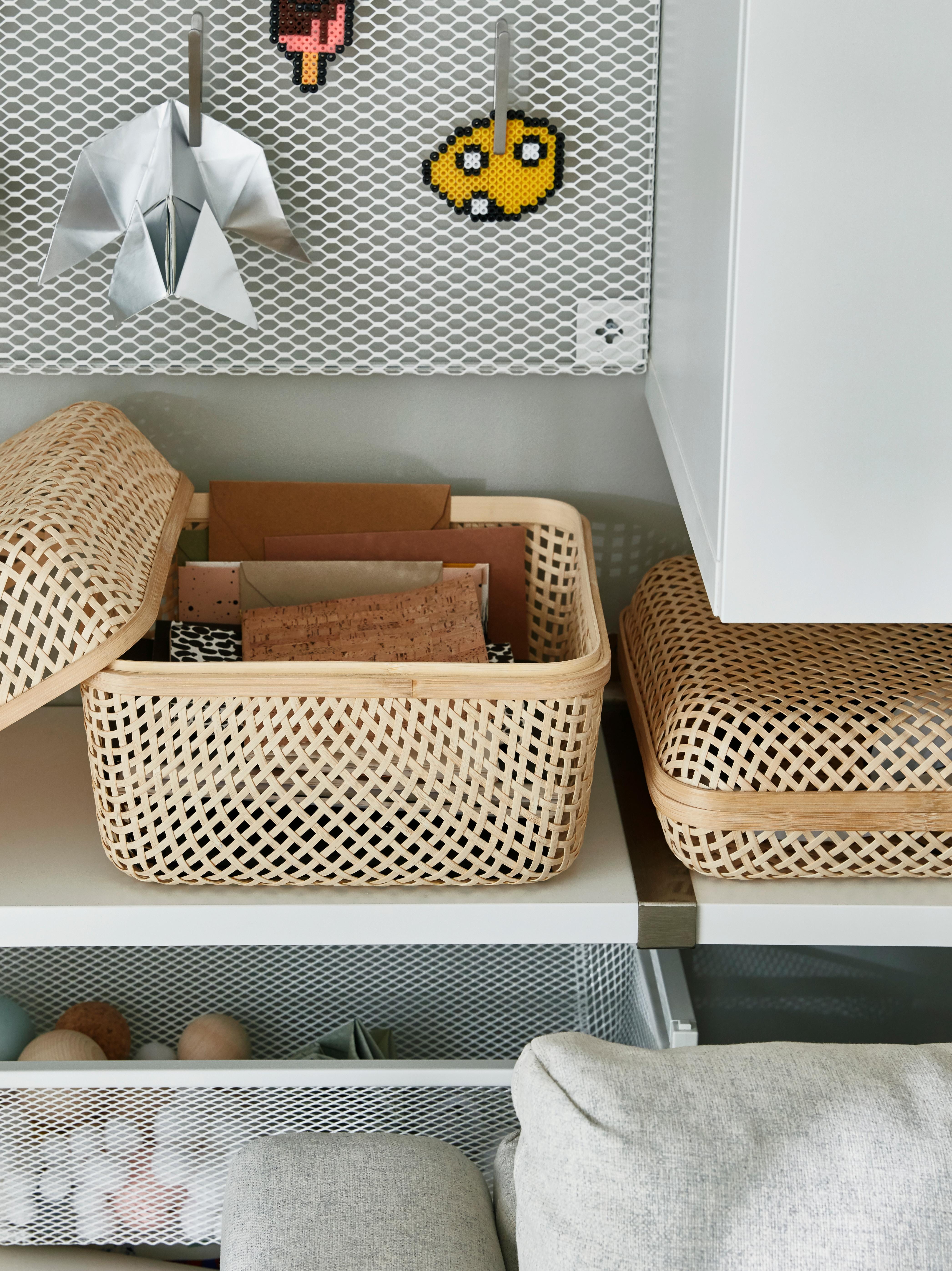 SMARRA kutija od tkanog bambusa s poklopcem nalazi se na polici pored odgovarajuće kutije druge veličine. Poklopac je skinut, a bilježnice su unutra.