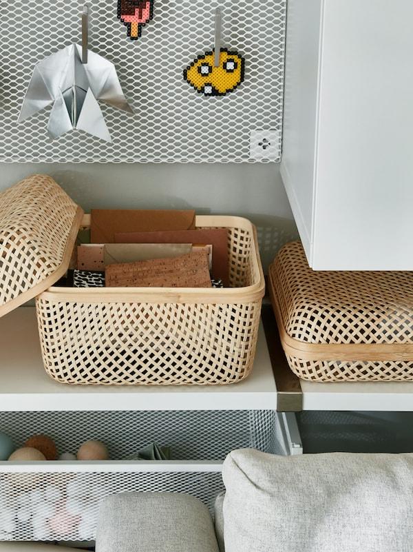 Des étagères contenant un panier tressé rempli d'objets en tout genre, au-dessus d'un support en maille blanche rempli de balles de couleurs variées.