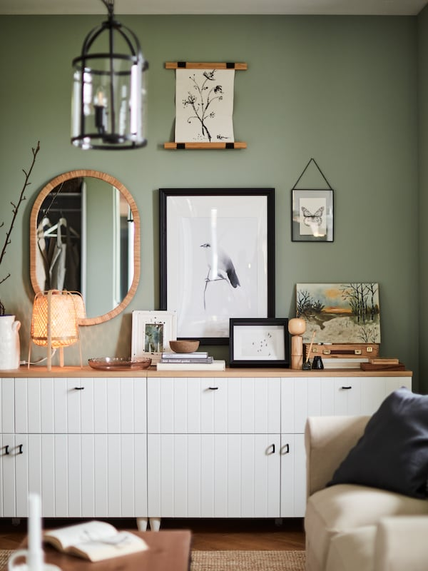 A mirror and some posters on a light-green wall above a display of various items on top of a white BESTÅ storage combination.
