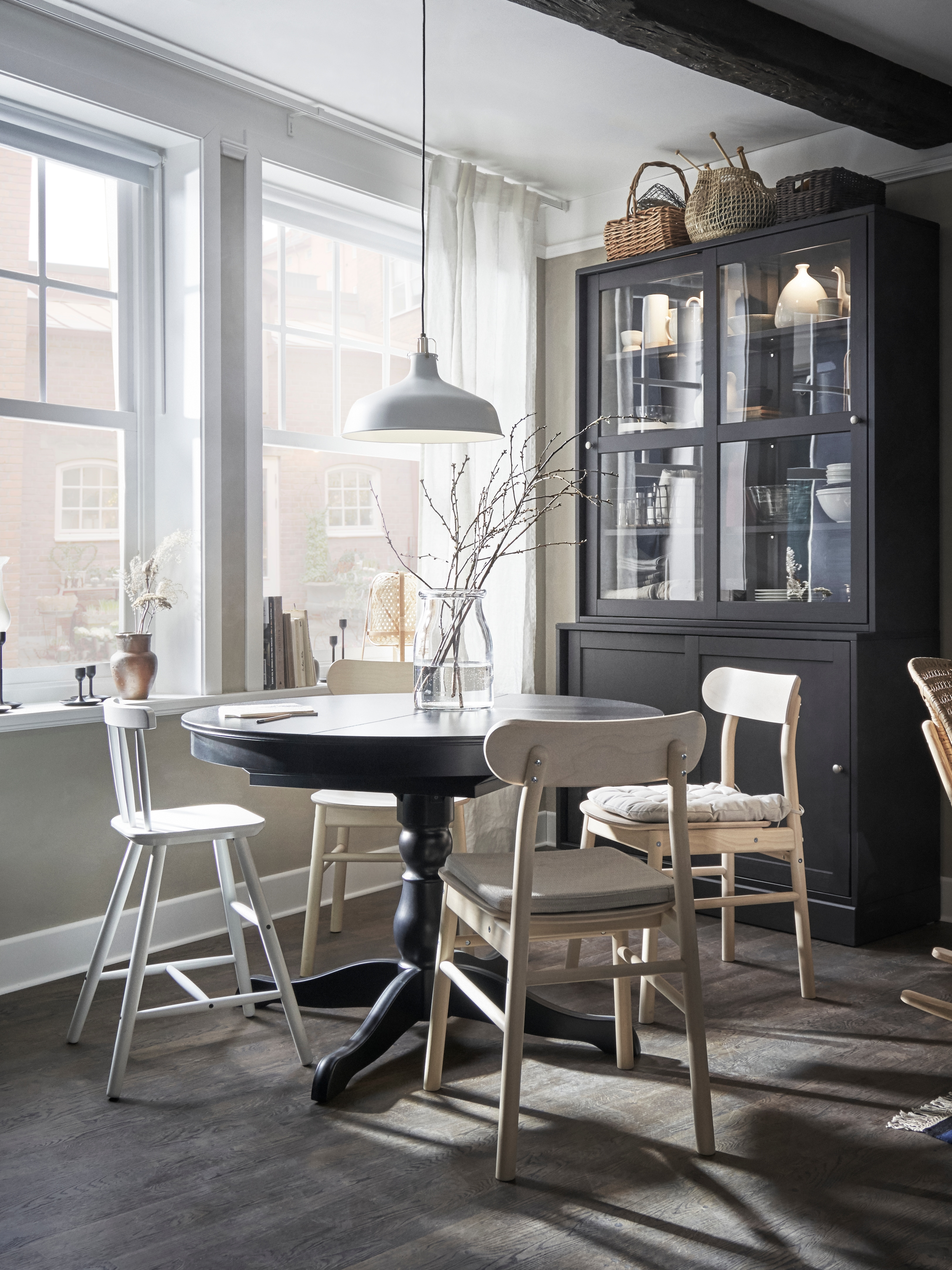 Dining area with extendable table, chairs, junior chair, pendant lamp, vase, storage baskets, storage unit with glass doors.