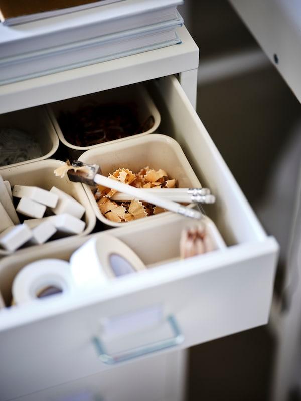 en vit  lådhurts med öppnade lådor där det förvaras pennor och annat, och ovanpå står diverse kontorsmaterial.