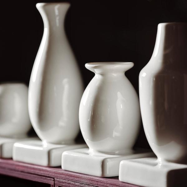 Ein Set aus vier weißen KRINGGÅ Vasen ist zu sehen; die Vasen stehen nebeneinander auf einem Regal in Rosa vor einem dunklen Hintergrund.