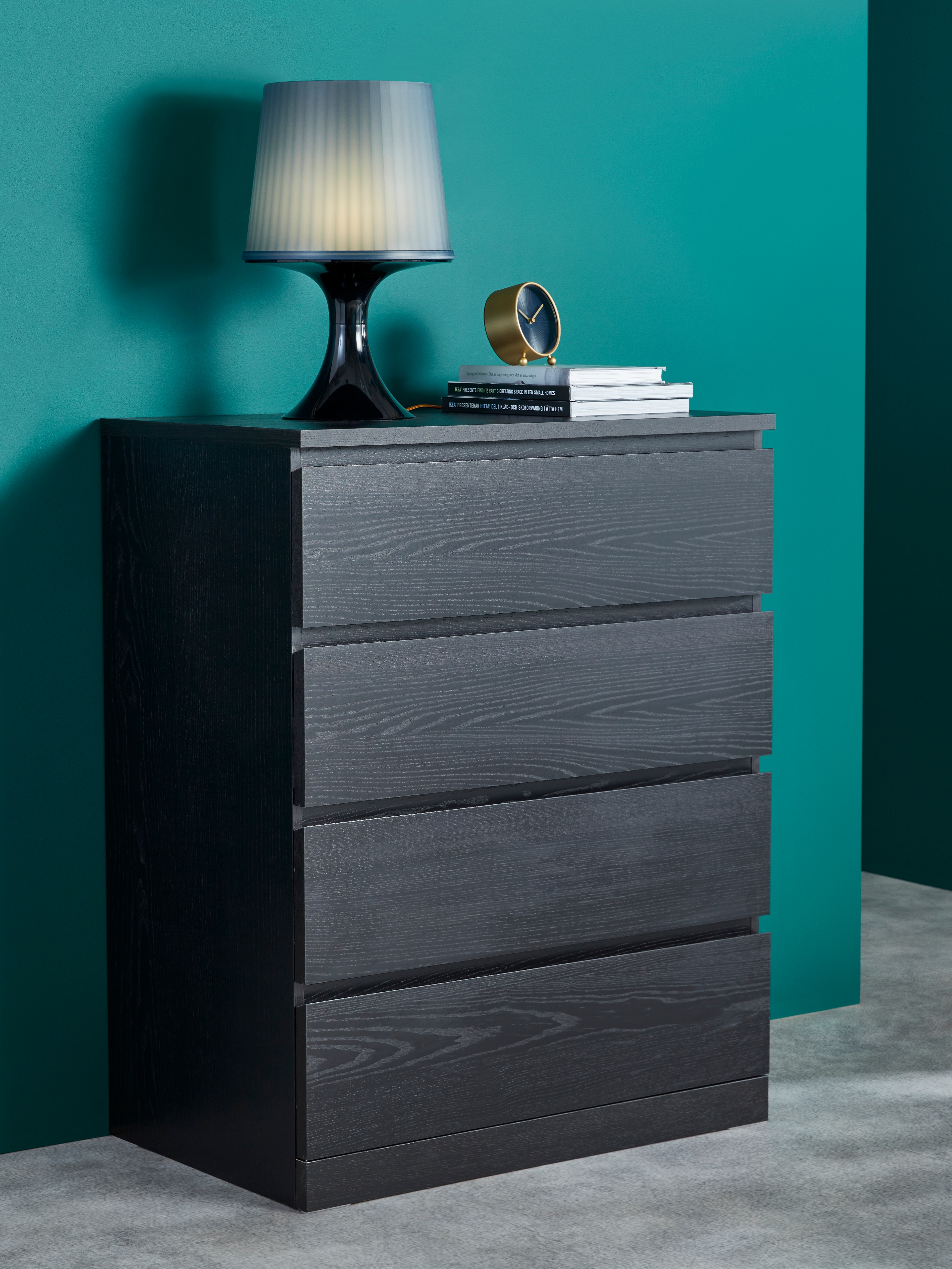 Room with green wall, black-brown chest of four drawers, dark blue table lamp, brass-coloured table clock.