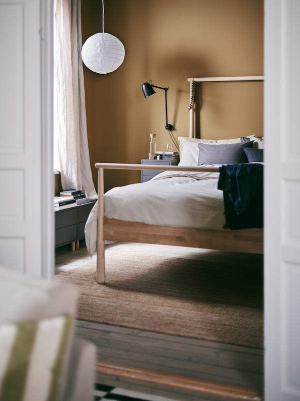 A glimpse into a warm and inviting bedroom with the GJÖRA bed in birch and REGOLIT pendant lamp shade made from paper.
