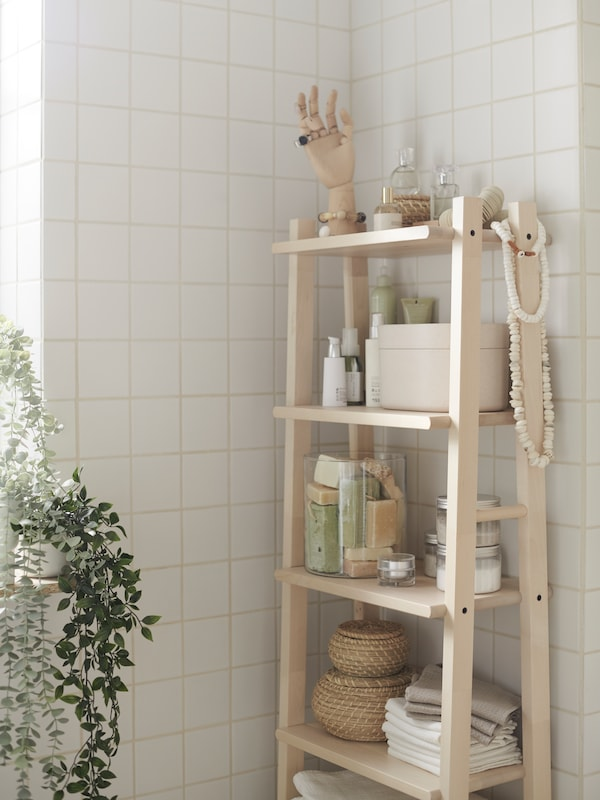 Bathroom with a VILTO shelving unit in solid birch with boxes, towels and a HANDSKALAD decoration hand for jewellery display.