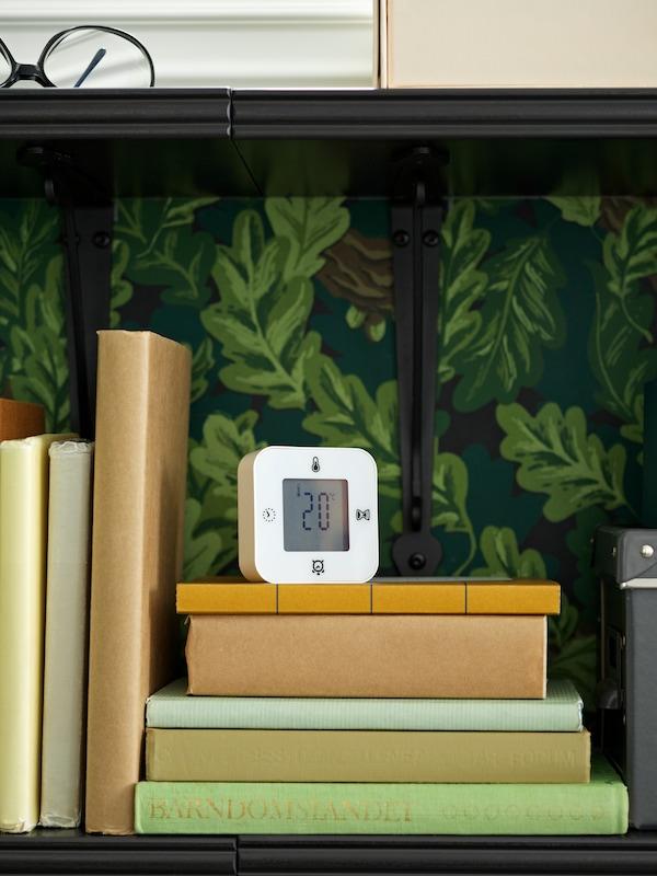 Un ceas/termometru/alarmă/temporizator KLOCKIS este așezat pe cărțile de pe un raft, indicând temperatura camerei.