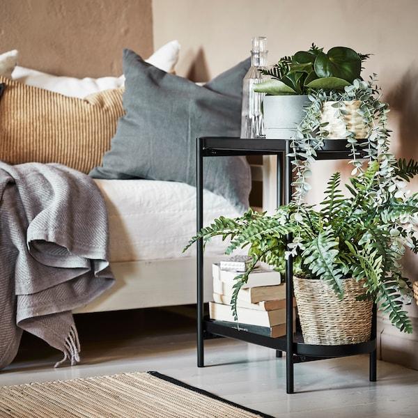 Pri pohovke je čierny stojan na kvetináče OLIVBLAD srozličnými izbovými rastlinami, kôpkou kníh afľašou vody.