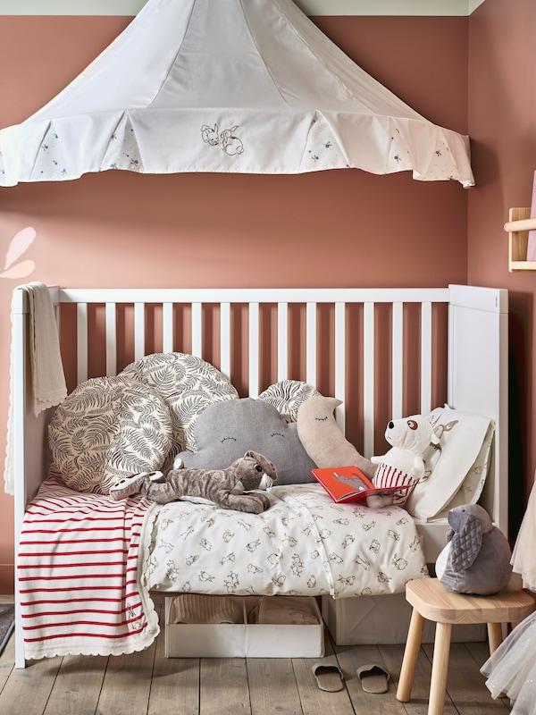 SUNDVIK spjälsäng där ena sidan tagits bort och RÖDHAKE påslakanset, kuddar och mjukleksaker under en RÖDHAKE sänghimmel.