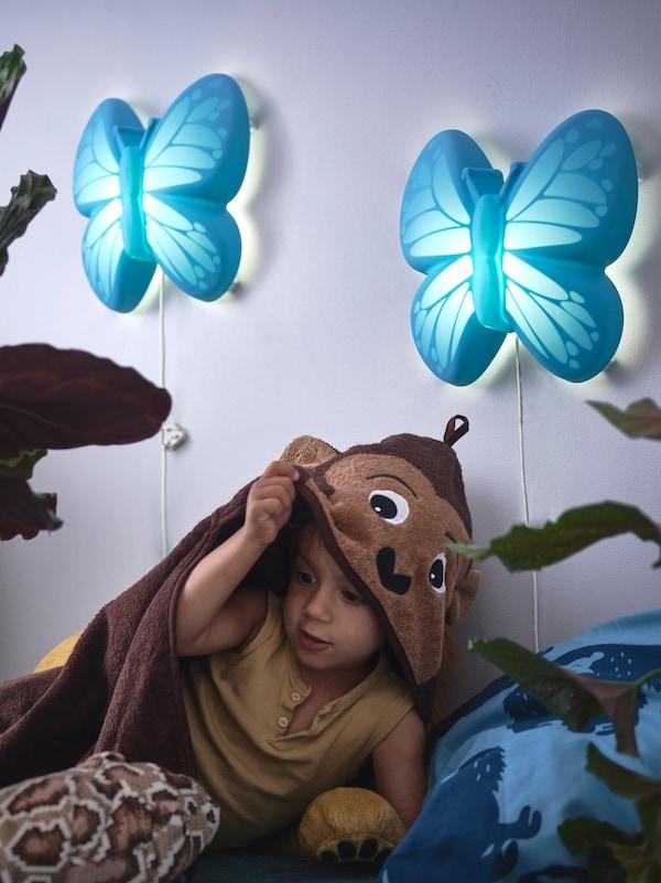 Dieťa pod prikrývkou, ktorá vyzerá ako opica, pod dvomi modrými nástennými lampami na svetlofialovej stene.