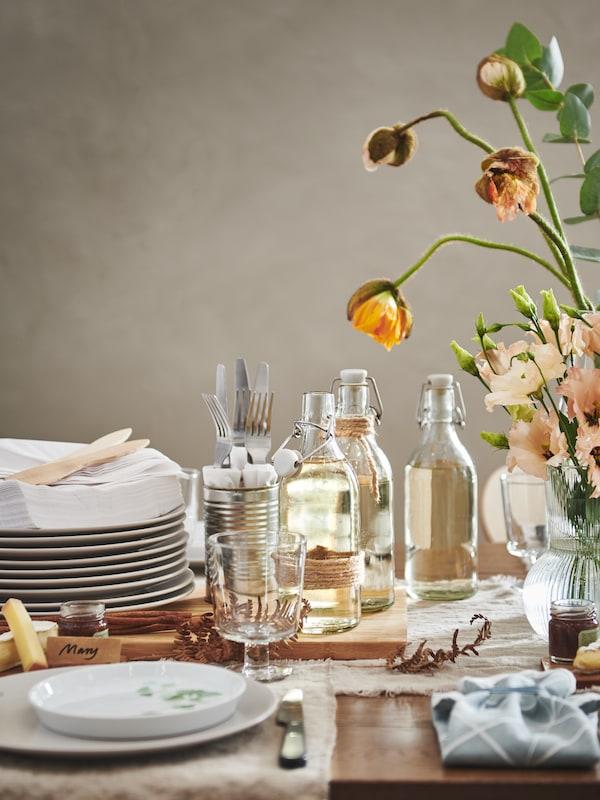STILENLIG dinnerware and KORKEN bottles on table setting.