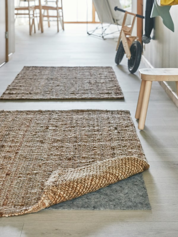 Two light brown woven rugs in a hallway by a wooden stool, one with the corner turned up, stopper underneath for safety.
