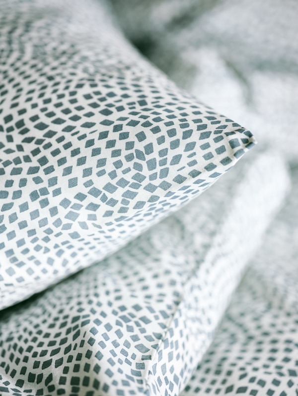 Le coin d'un oreiller posé au-dessus d'un autre oreiller et d'une couette, le tout recouvert du linge de lit bleu et blanc TRÄDKRASSULA