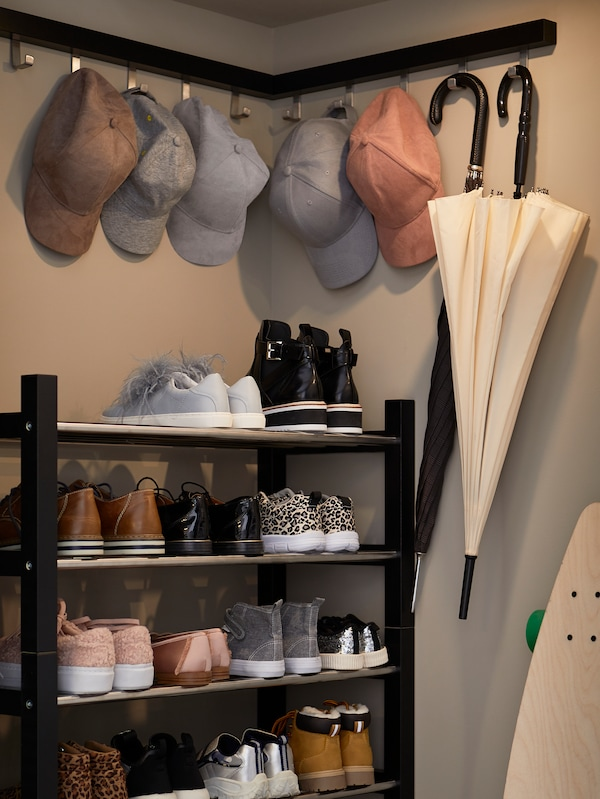A corner in a built-in wardrobe where caps and umbrellas hang from hooks above TJUSIG shoe racks filled with shoes.
