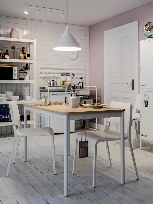 Lunchroom con pareti rosa e piastrelle bianche, tavolo da pranzo, sedie bianche, lampada a sospensione, porta bianca.