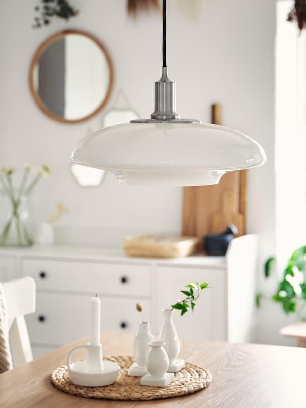 Nad mizo iz hrastovega furnirja, na kateri so bele vaze, visi ponikljana svetilka z belim steklenim senčnikom.