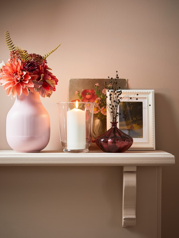 A shelf decorated with a pink vase, a lit candle, and frames.