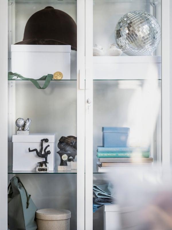 Una vetrina con un caschetto da equitazione, una sfera da discoteca, contenitori, libri e alcune statuette - IKEA