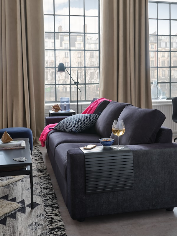 Un salon bien éclairé et aéré. De grandes fenêtres ouvertes avec des rideaux beiges tirés. Un canapé gris foncé avec un jeté rose et un coussin à motifs. Un plateau en bambou pour accoudoir sur lequel sont posés un verre de vin et un bol.