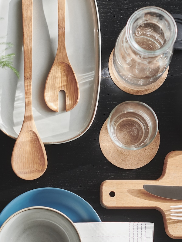Part of a table top on which there are coasters, crockery, glassware and a grey GLADELIG plate with salad servers.