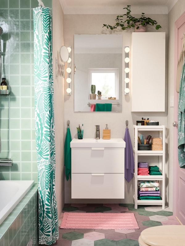 مغسلة على وحدة حوض غسلGODMORGON تحت شباك. مصابيح على الحائط وعربة إلى جانب وحدة حوض غسل.