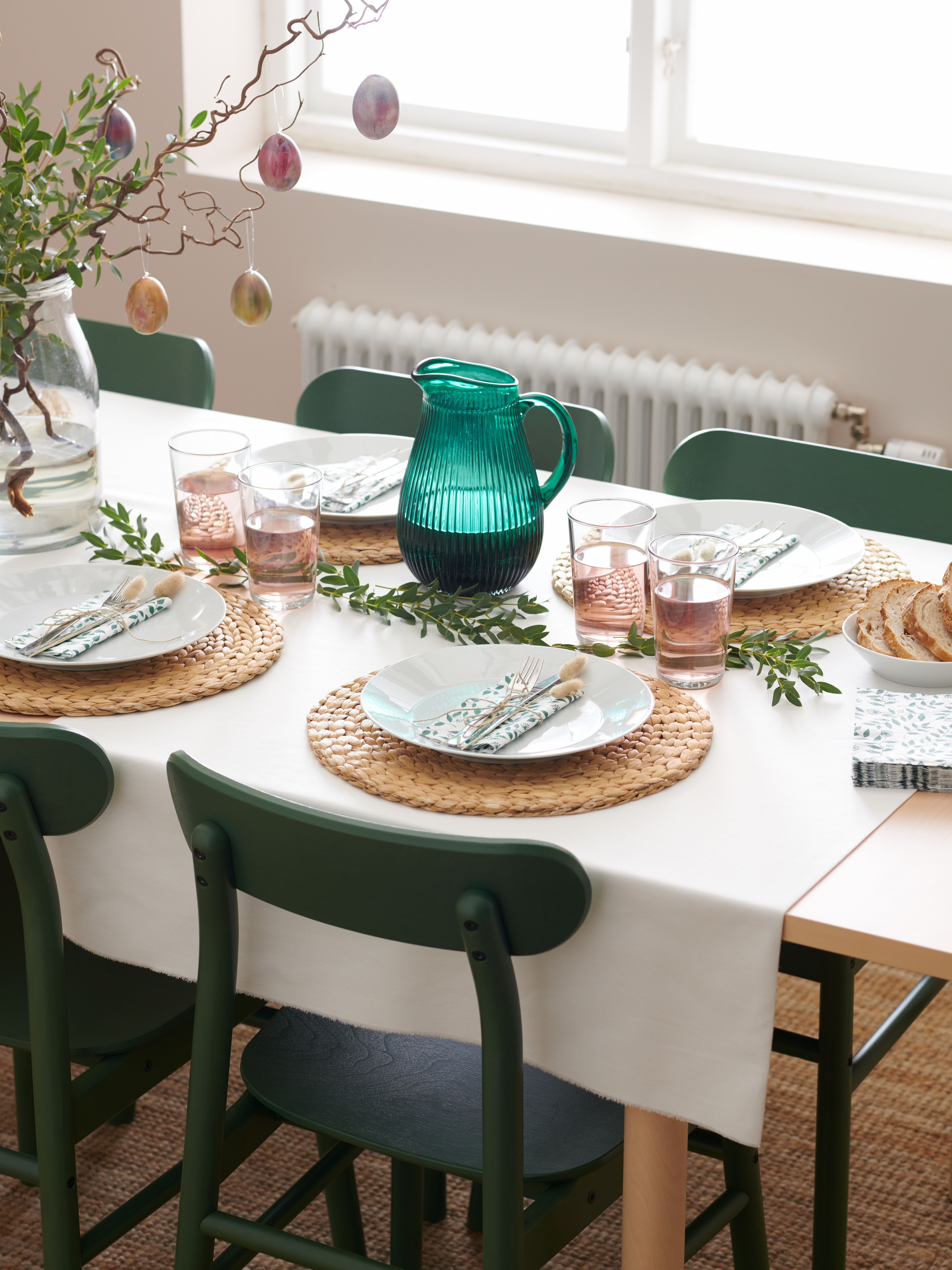 Un tavolo è decorato e apparecchiato per la Pasqua con stoviglie, tovaglioli e uova colorate appese a rametti.