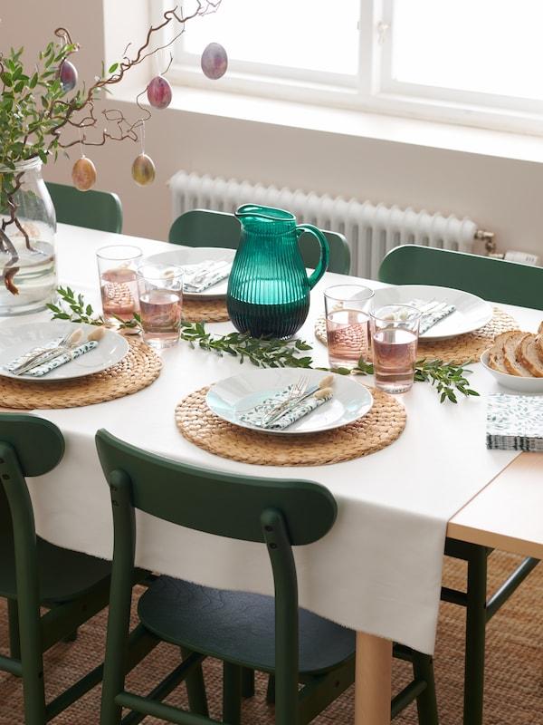 Two leaf patterned white/green STILENLIG bowls, one containing olives, sit on a BONDHOLMEN outdoor table.