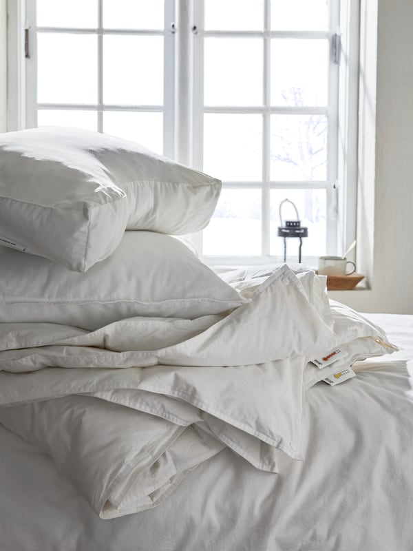 A casually folded white duvet cover and pillows, placed on a bed in a sunlit room.
