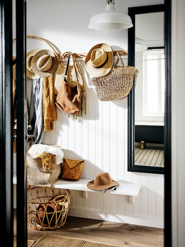 An inviting hallway with a small bench and rattan baskets for storing hats and handbags.
