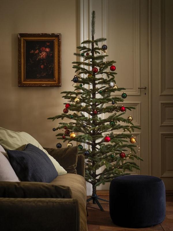 Karácsonyfa gömbökkel és más díszekkel, egy kanapé és egy lábtartó mögött, egy ajtó előtt.