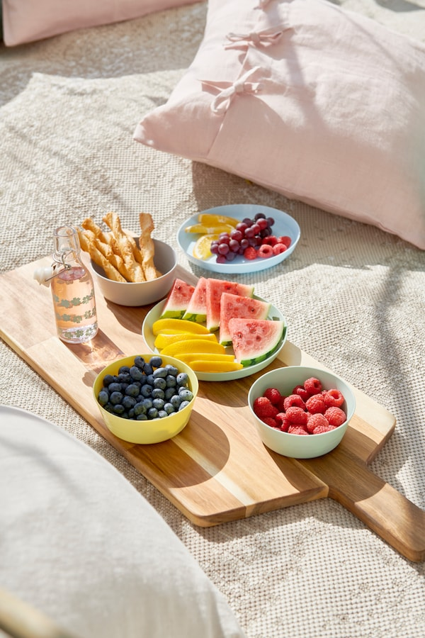 A cutting board with KALAS plates and bowls filled with a variety of fruit.