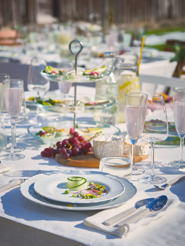 A table set with white tableware, on which food is arranged on plates and etagères standing on a white tablecloth.