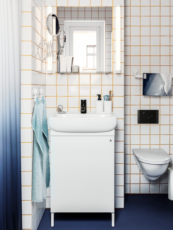 Kabinet sink cuci tangan berwarna putih, paip berwarna hitam, cermin, jubin berwarna putih dengan turap berwarna kuning, pencangkuk dengan tuala.