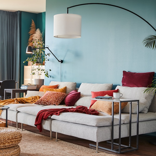 A sofa with cushions in diverse colors in it, two throws and lighting mounted on a green wall and a lamp hanging above.