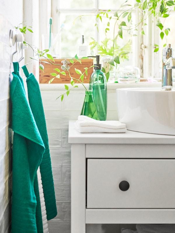 Două prosoape de mâini verzi VÅGSJÖN suspendate de cârlige cu ventuze lângă un lavoar cu o vază verde.