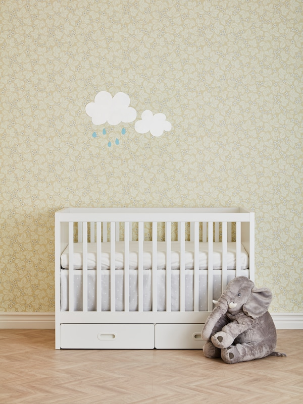 A white crib against a patterned wall with two rain cloud stickers, and an elephant soft toy on the floor.