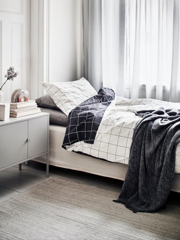 Dormitorio con cortinas blancas traslúcidas por las que se filtra algo de luz solar. La cama está hecha con ropa de cama VITKLÖVER y una manta INGRUN.