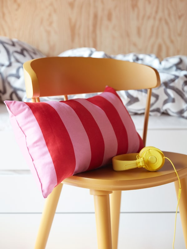 A yellow chair, headphones, and a pink-red striped SARAKAJSA cushion in front of a bed with white-gray bed linen.