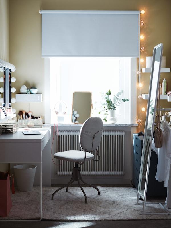 Ein beiger Drehstuhl an einem weissen MICKE Schreibtisch. Daneben ist ein Tischspiegel und auf der Fensterbank eine Pflanze zu sehen. Auch ein weisser Standspiegel ist im Bild.