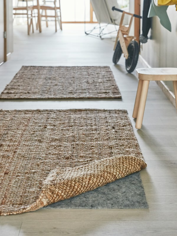 Two light brown woven rugs in a hallway, the corner of one turned up, with a stopper underneath for safety.
