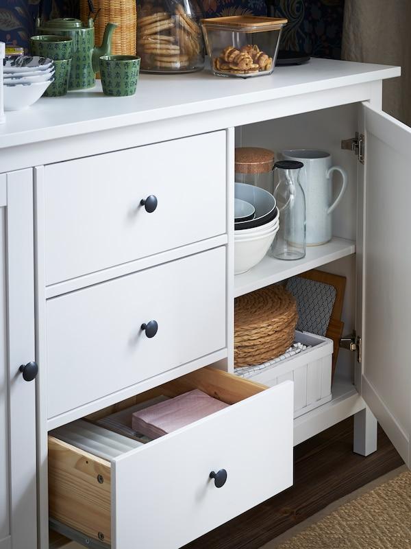 Jarros, tigelas, individuais, guardanapos de papel e outros artigos guardados e sobre um aparador HEMMES em branco com três gavetas.