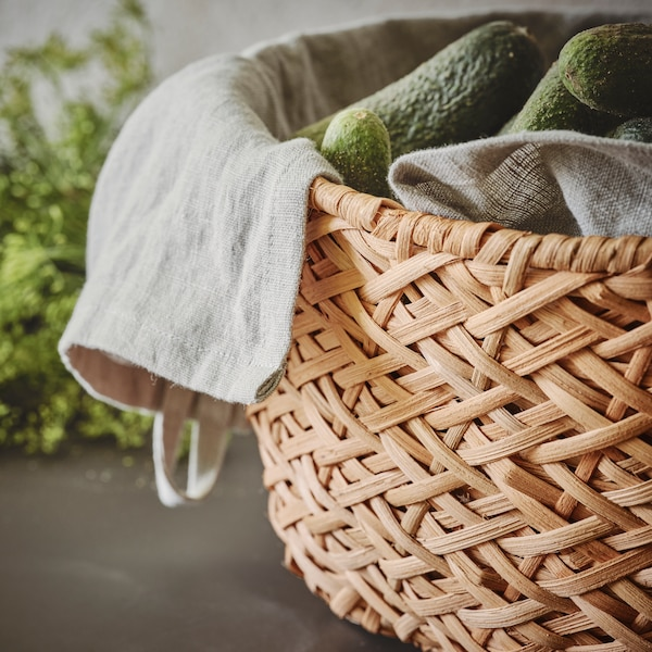 A rattan TJILLEVIPS basket containing white washcloths and cucumbers sits on a floor in front of a green plant.