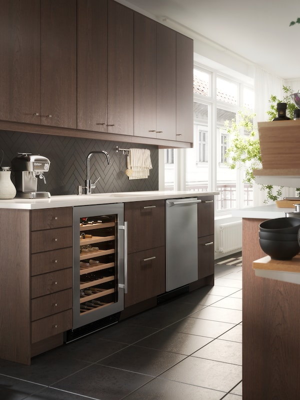 An open-plan kitchen with SINARP fronts in brown, NUMRERAD wine cooler and an ESSENTIELL dishwasher in stainless steel.