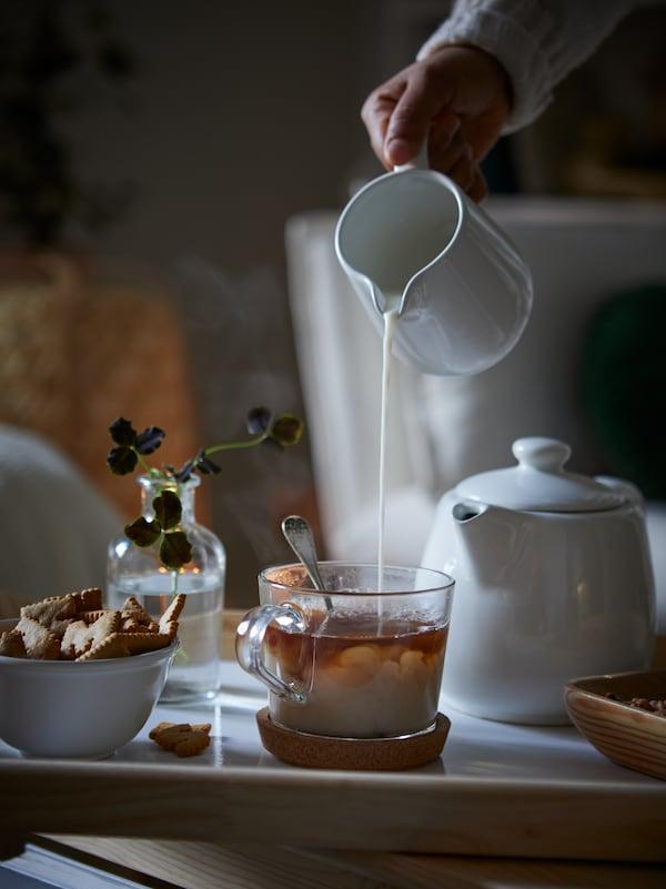 une personne verse du lait dans une tasse de thé posée sur une table basse