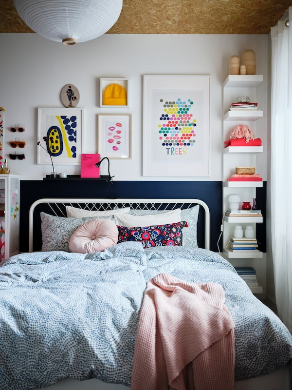 A bedroom in light shades and colourful decorations, and a white NESTTUN bed made with blue-and-white TRÄDKRASSULA bed linen.
