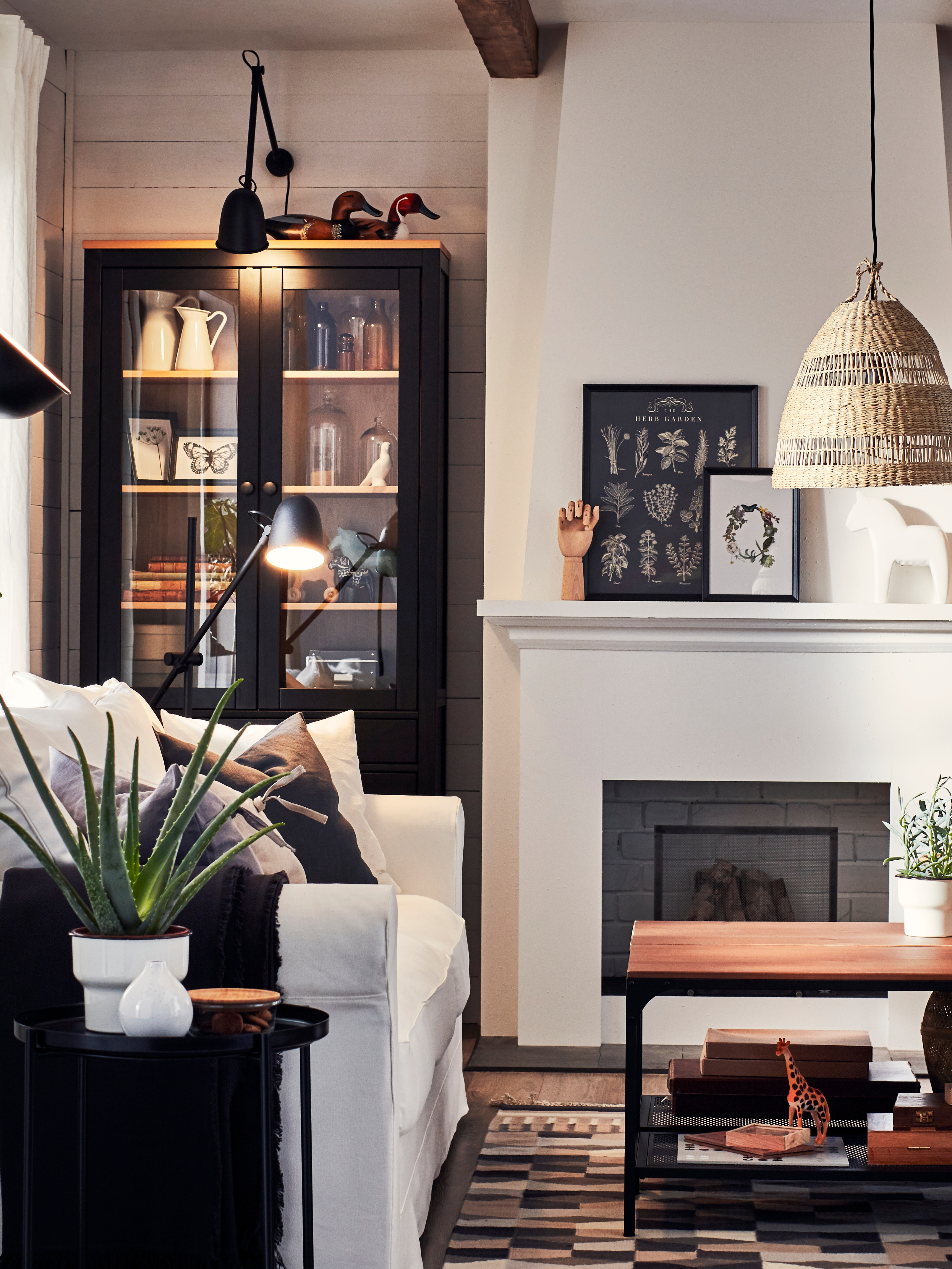 A white sofa and black wooden bookcase are illuminated by a black SKURUP work/wall lamp and matching floor lamps.