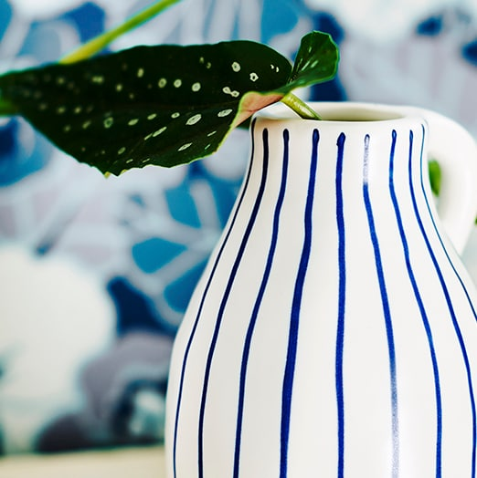 A blue and white striped jug, holding a green, leafy plant stem.