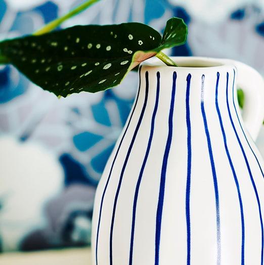 Plavo-bijeli prugasti vrč sa zelenom stabljikom s listom biljke.
