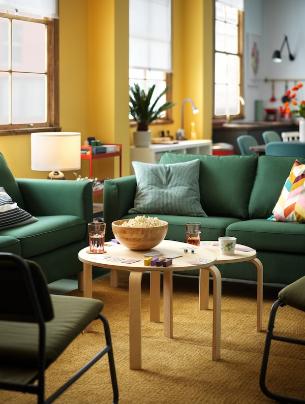 Two green PÄRUP sofas, combined with two LINNEBÄCK easy chairs to form a square, with two nest tables at the centre.