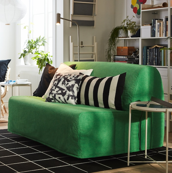 A room with a Vansbro bright green LYCKSELE LÖVÅS two-seat sofa-bed, black and white textiles, white bookcases, an armchair.
